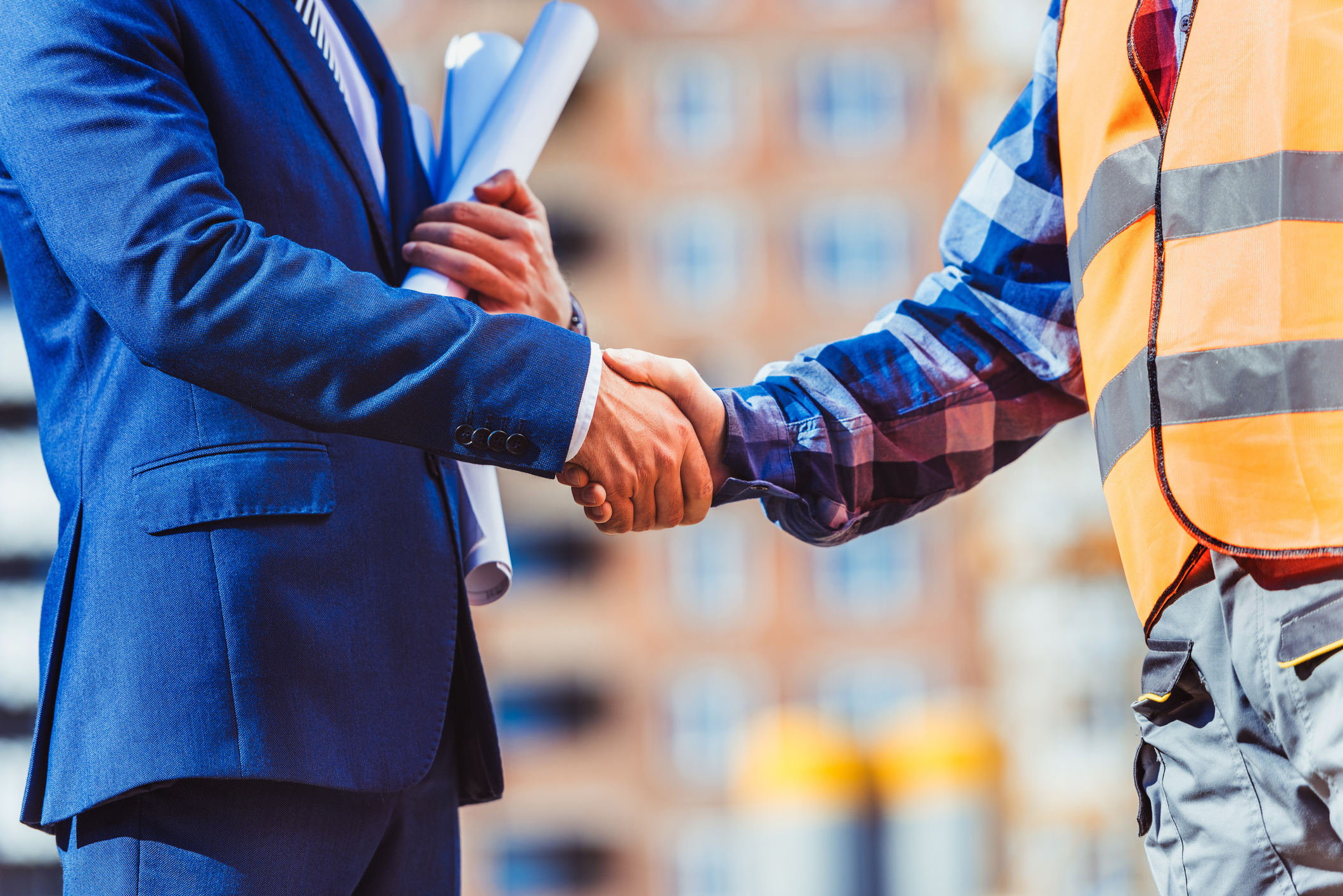 Cropped shot of construction worker in reflective vest shaking hands with businessman